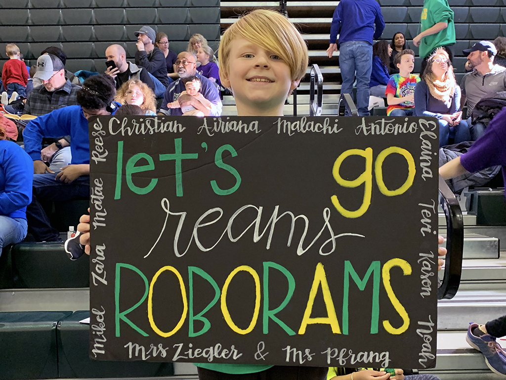 Student at robotics competition holding up a homemade sign saying 'let's go Reams Roborams!'.