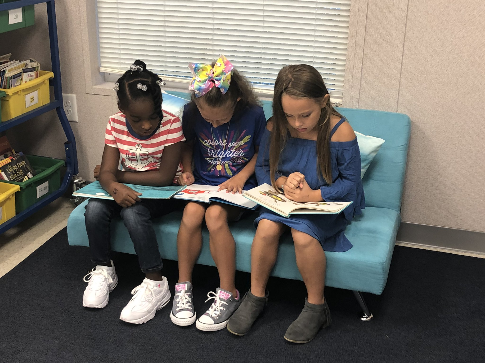 Three students sitting on a sofa reading their books.