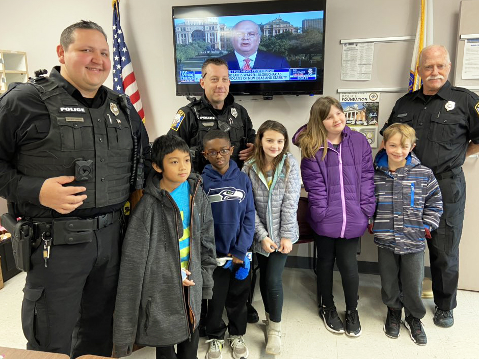 Five students pose for a photo with three police officers.