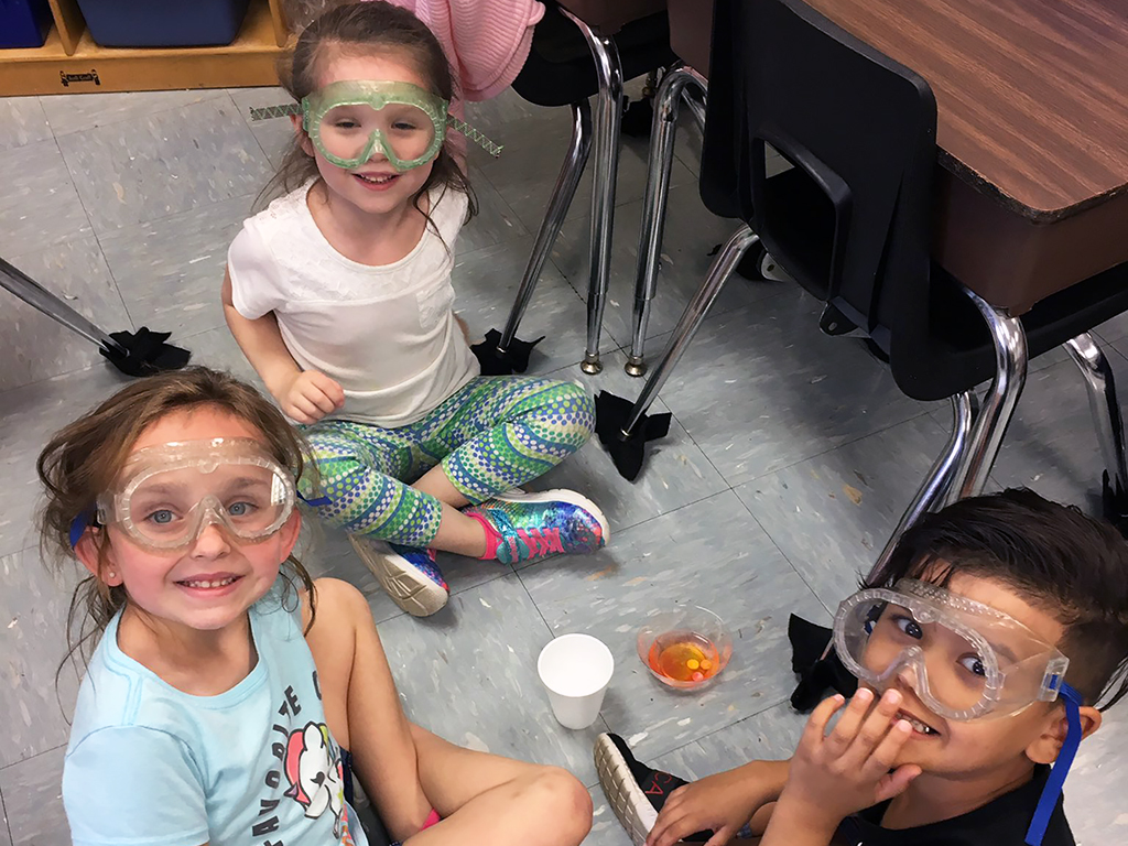Three students sitting on the floor looking up at the camera wearing goggles.