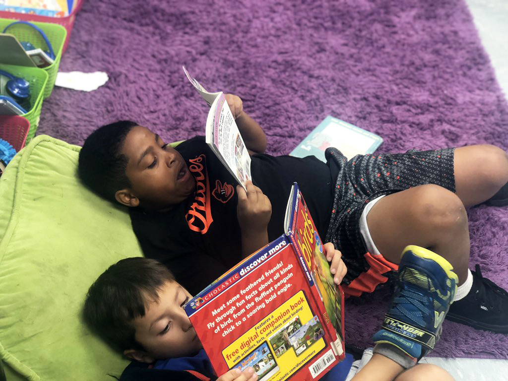 Two male students laying on a bean bag chair while reading their books.