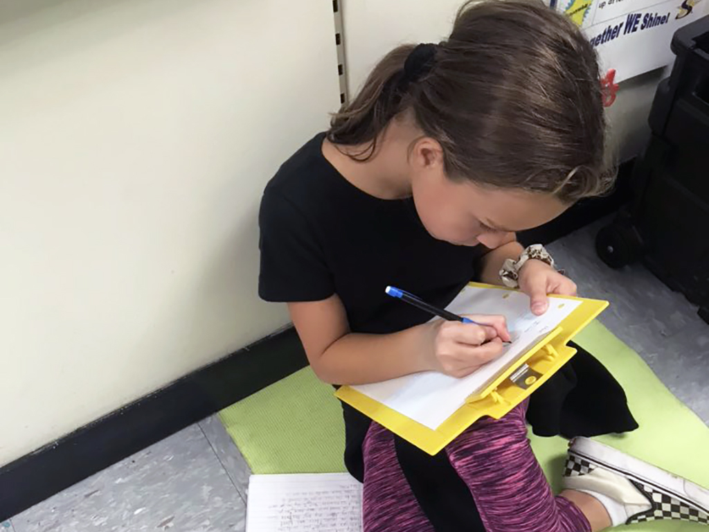 Female student sitting on the floor working hard on a paper.