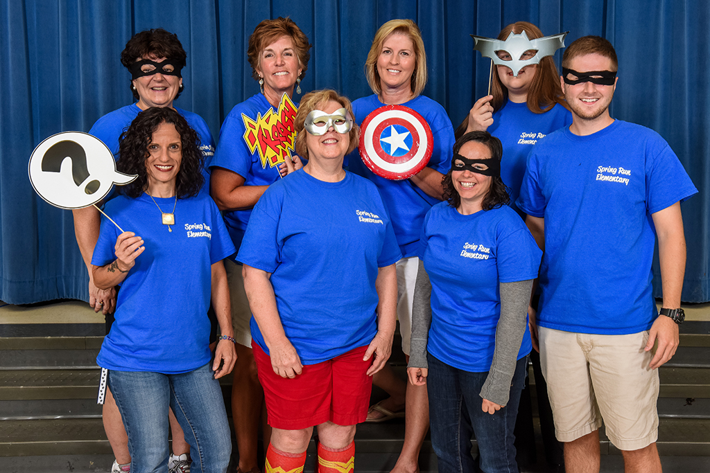 Group of eight PE teachers pose in matching t-shirts and with superman props.