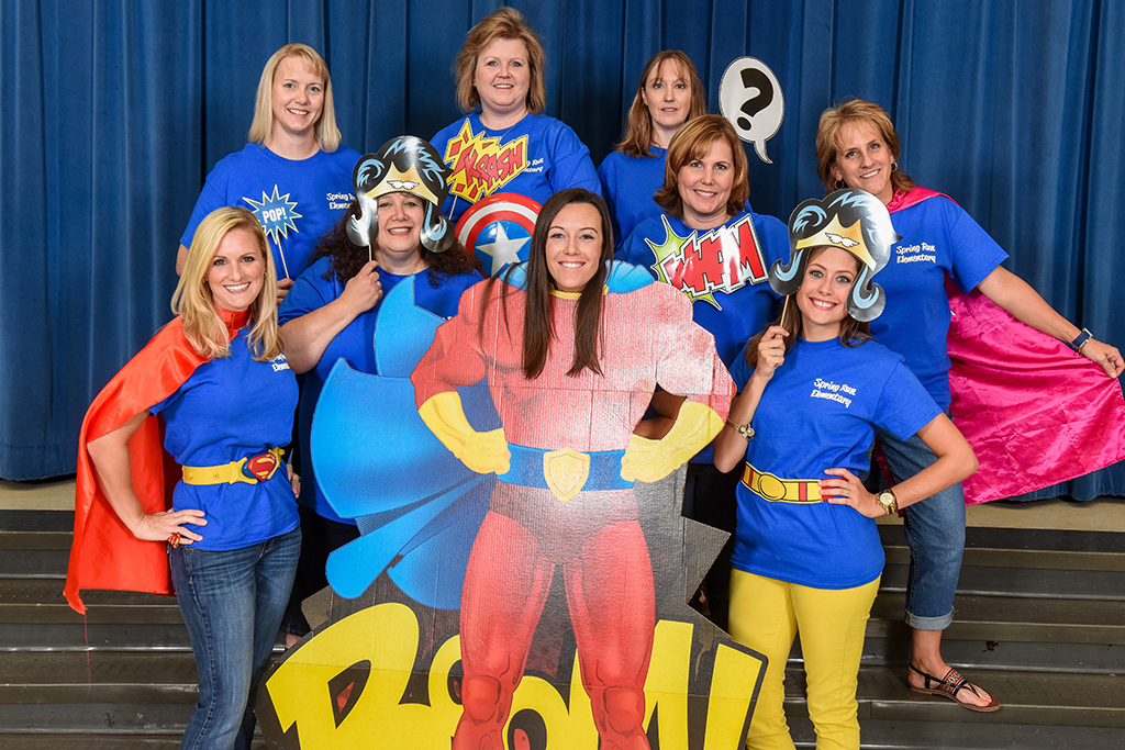 Group of eight teachers dressed like superwoman posing with a cutout of superwoman.