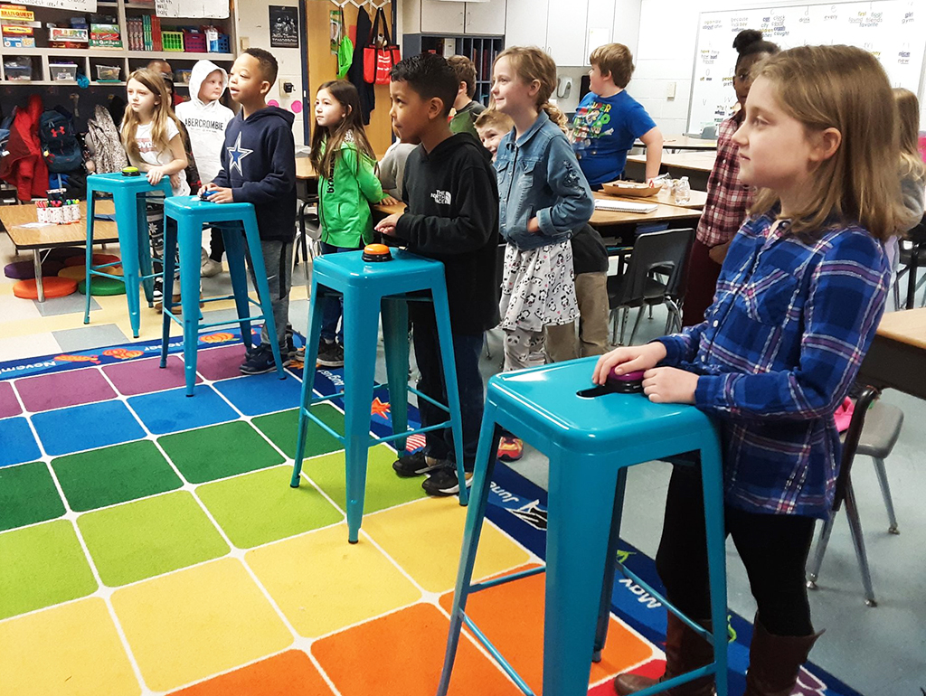 Students stand at stools and looking at chalkboard while practicing math.