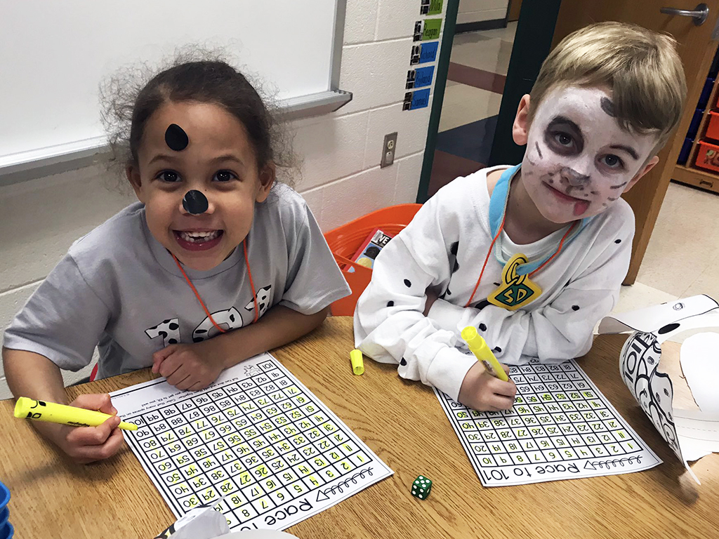 Two students with black and white dog face paint on working at their table.