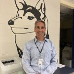 Selfie of Mr. Gardner with mascot painted on the wall behind him.