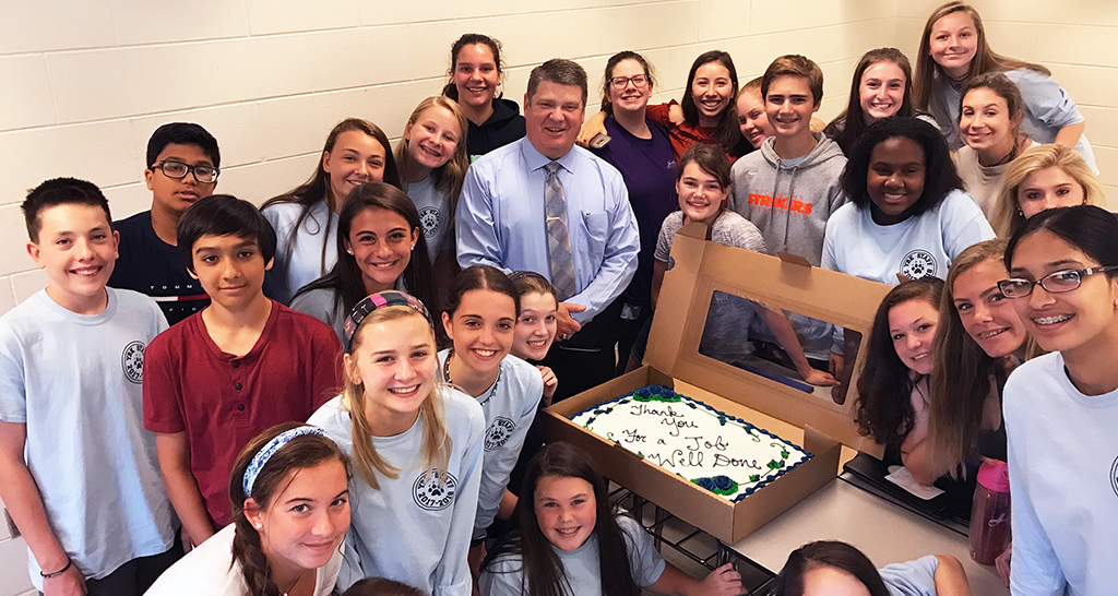 Dr. Ellena with a large group of students presenting him with a thank you cake!
