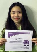 Student holding award certificate and smiling.