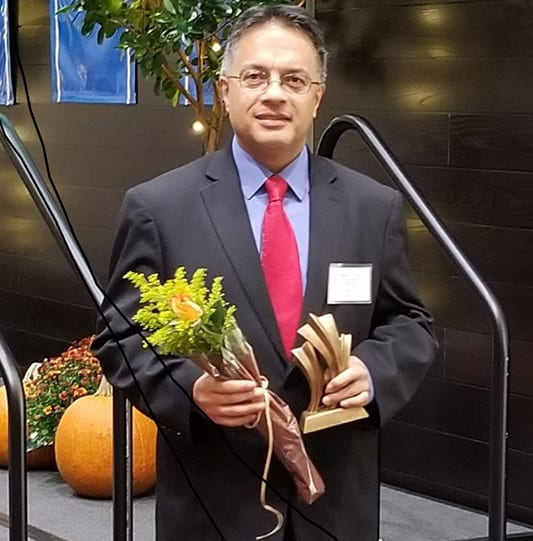 mr garavito holding flowers and his award