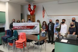 Teacher standing with family and leadership staff holding a giant congratulations banner.