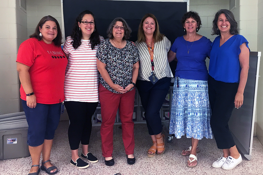Six female teachers lined up to pose for a photo.
