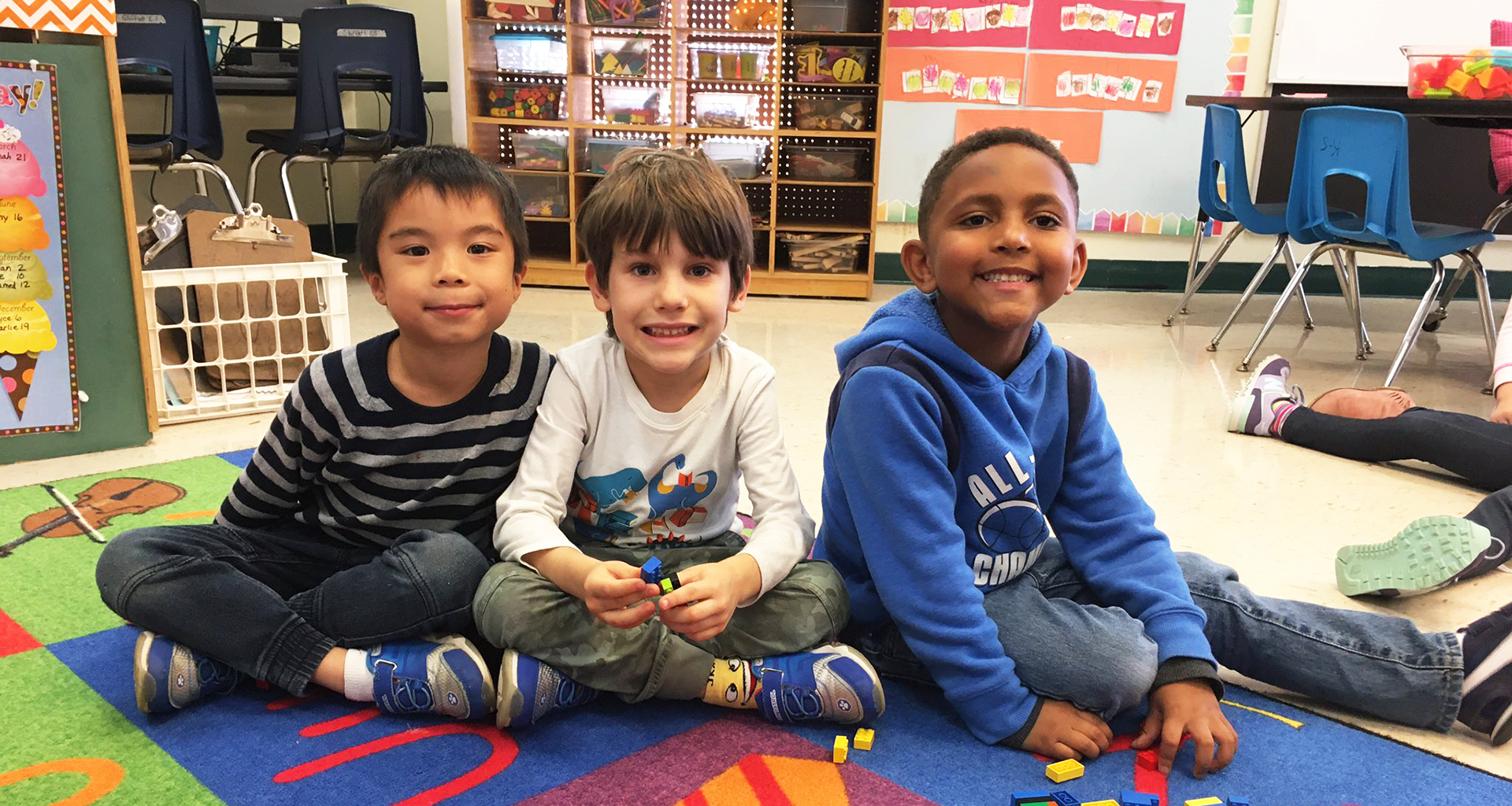 Three boys sitting on carpet working on building with blocks.