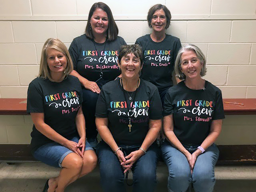 Group of five teachers in matching t-shirts pose for a photo.