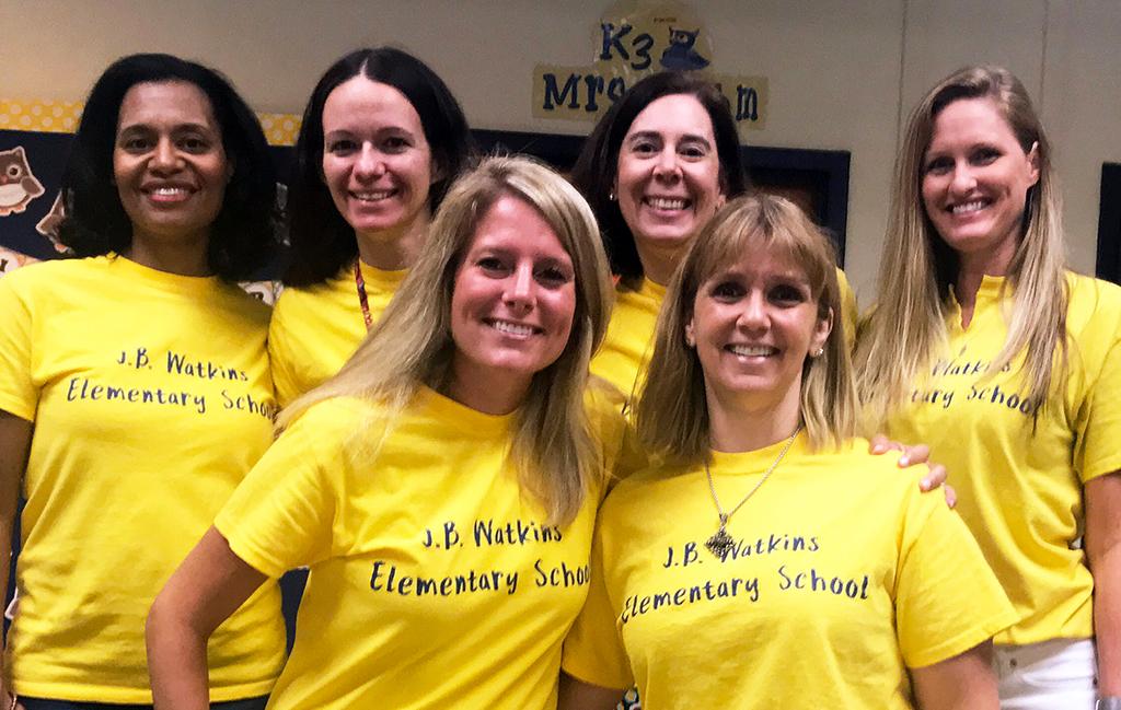 Six teachers wearing matching yellow t-shirts pose for a photo.