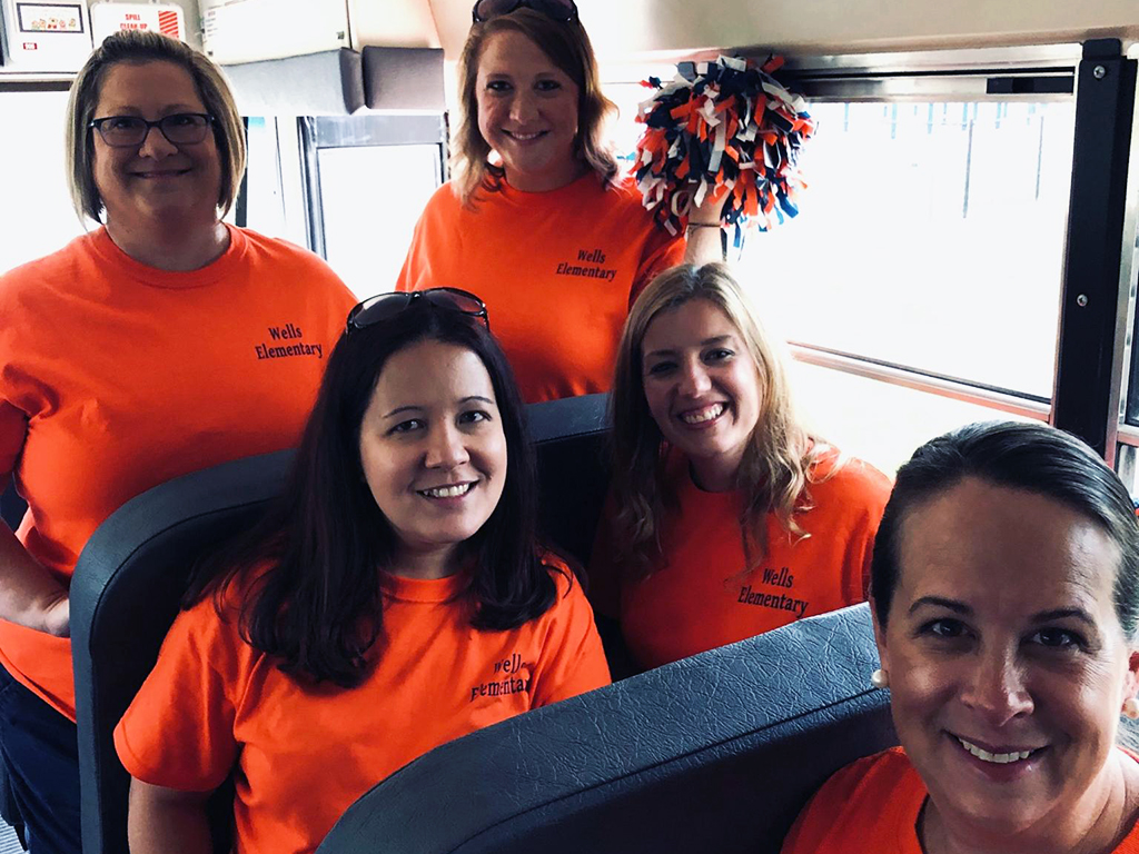 Five female teachers sitting on a school bus pose for a photo.