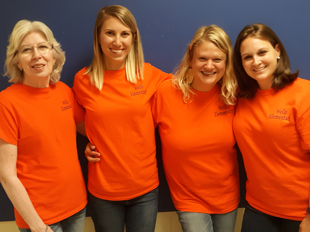 Four female teachers in matching t-shirts pose for a photo.