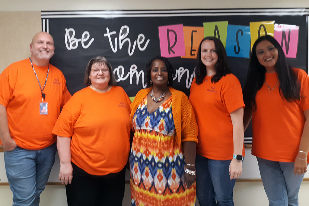 Five teachers pose for a photo in a classroom.