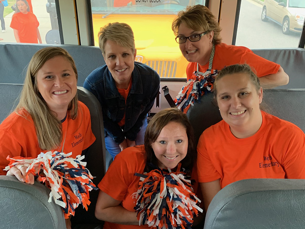 Five female teachers pose for a photo on a school bus.