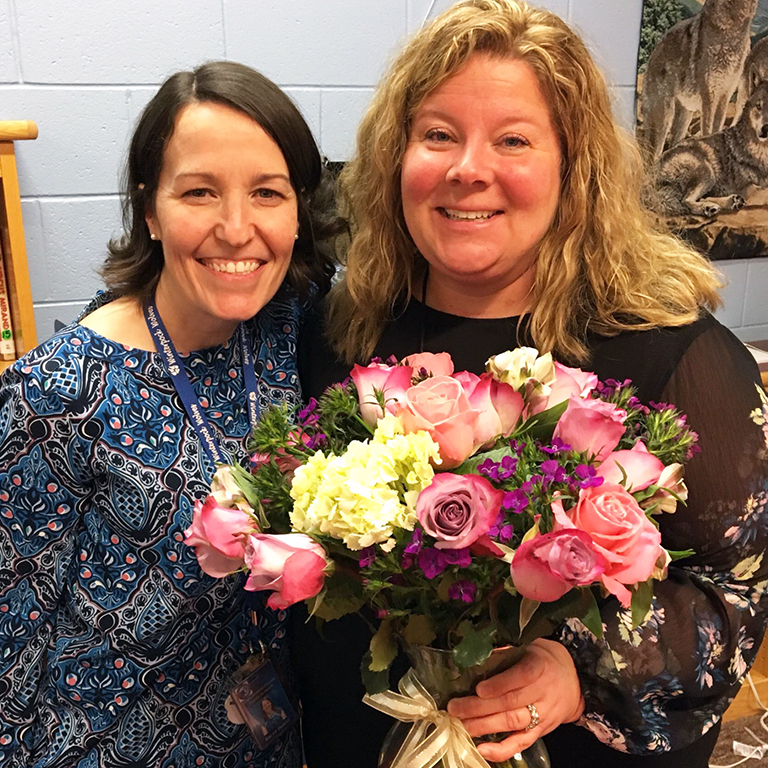 Photo of Ms. Husick holding flowers with the principal