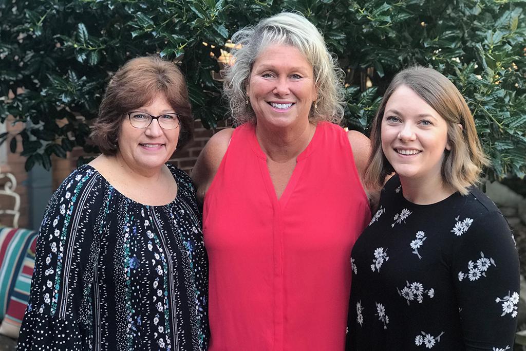 Three teachers pose for a photo.