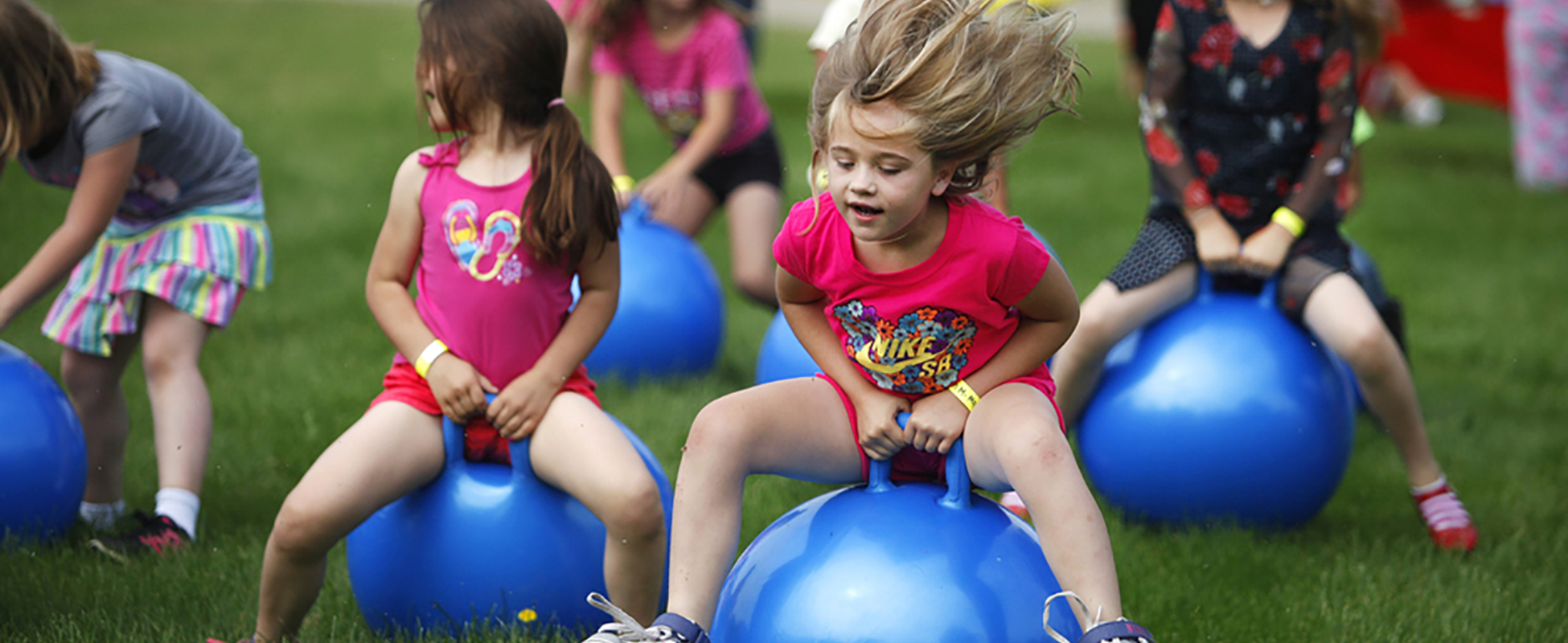 students outside bouncing on top of a large ball