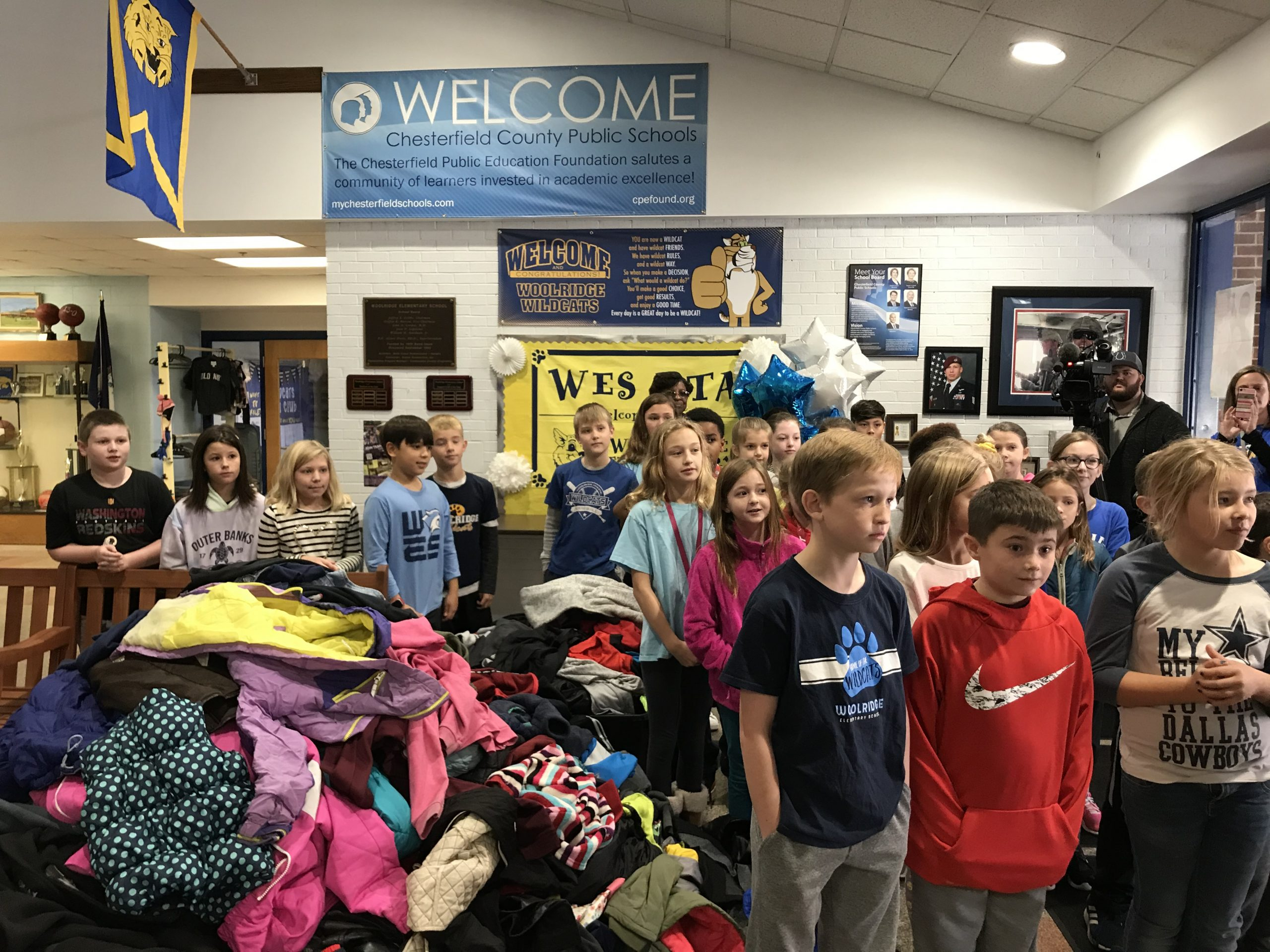 Students in room filled with coats they are donating.