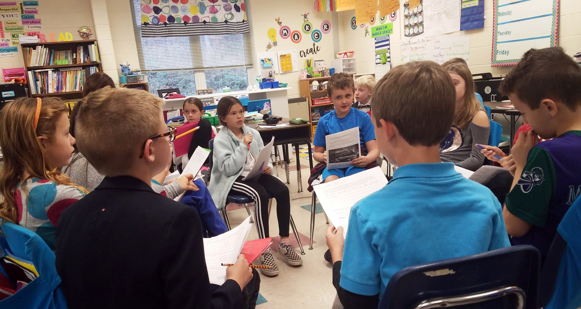 Students sitting in a circle in their classroom discussing a project.